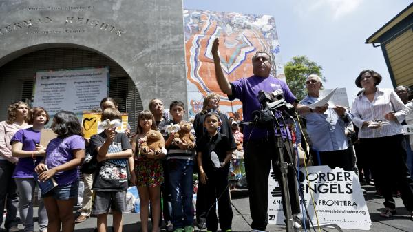 Human-rights activist Enrique Morones, at podium, speaks during a rally in support of immigrants on Wednesday in San Diego. A group of about 70 people rallied in support of migrant children and families Wednesday, a day after U.S. Homeland Security buses carrying the migrants were routed away from American flag-waving protesters in Murrieta, Calif., and transported to a facility in San Diego.