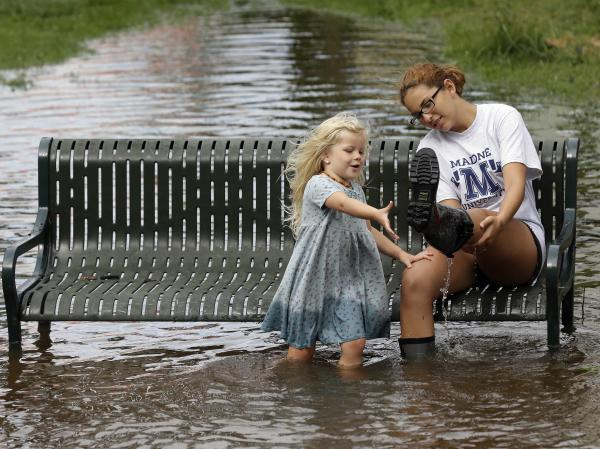 Katie Bender gets some assistance from Johanna Bender, left, as they dump water from a boot while sitting on a flooded street after Hurricane Arthur passed through in Manteo, N.C., on Friday.