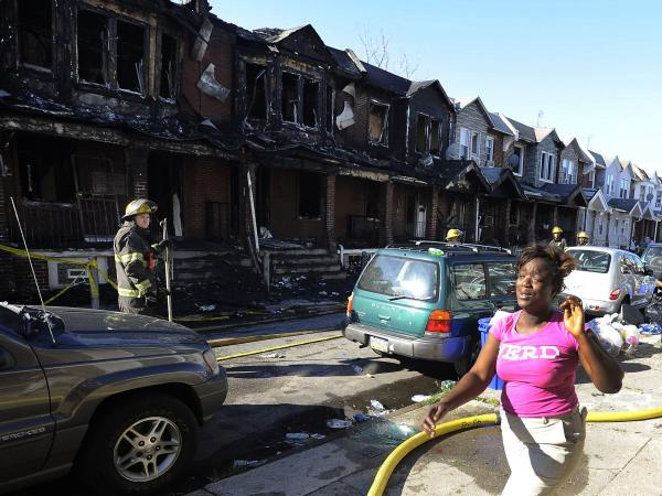 A woman cries as she walks past Philadelphia firefighters working on burned row homes on Saturday.