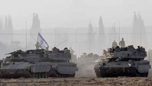 Israeli soldiers stand on their tanks near Israel's border with the Gaza Strip on Tuesday. Israeli warplanes pounded Gaza with more than 50 strikes overnight after Hamas militants fired scores of rockets over the border.