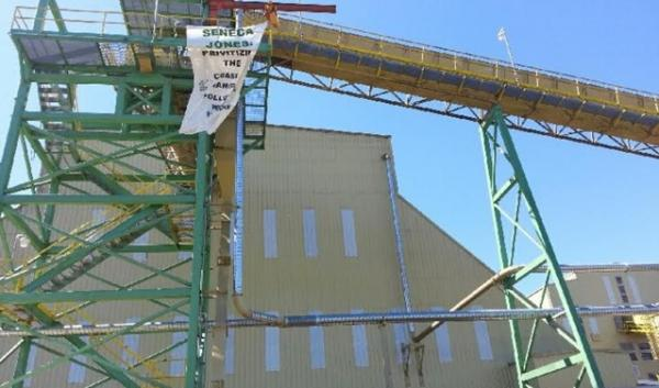 Protesters hung a banner from equipment at the Seneca plant Monday Morning.