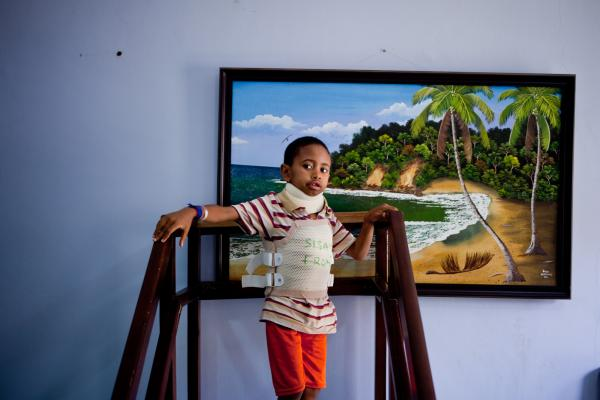 "Sisay stands at the top of a physical therapy stair. He spent months away from his family at the Accra hospital undergoing a spine-stretching treatment, surgery and recovery. ""Ghana is too hot,"" says the young boy from Ethiopia."