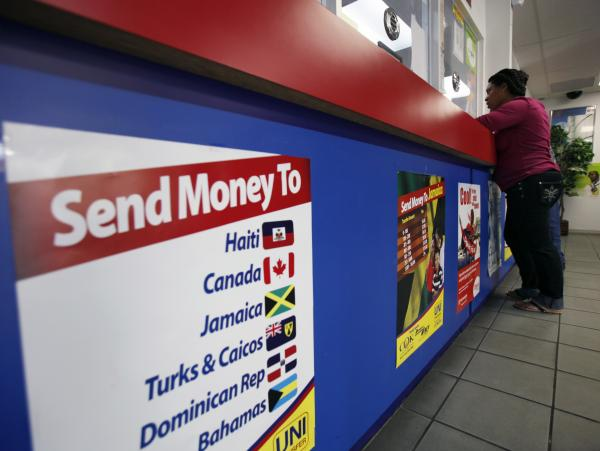 A customer stands at the counter at Unitransfer, a money transfer company at the Little Haiti neighborhood in Miami, Fla.
