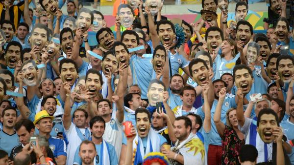 Uruguay's fans hold up cut-out images of forward Luis Suarez in Rio last month. The striker's World Cup ended in embarrassment, but he'll have a chance to start over in Barcelona.