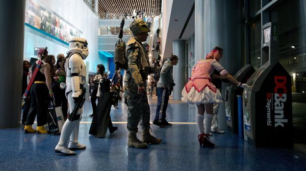 Anna Swope, dressed as a stormtrooper from <em>Star Wars</em>, and her husband Stephen Goss, dressed as the films' Boba Fett, wait to use an ATM while attending the Fan Expo convention in Vancouver, B.C.