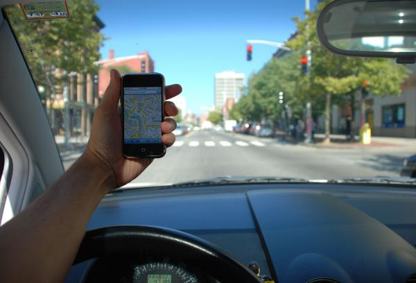 A driver holds an iPhone with Google Maps while at a red light. (Steve Garfield/Flickr)