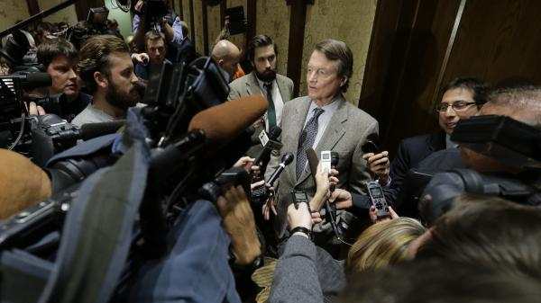 University of Texas, Austin President Bill Powers (center) speaks  with the media following a December 2013 regents meeting in Austin.