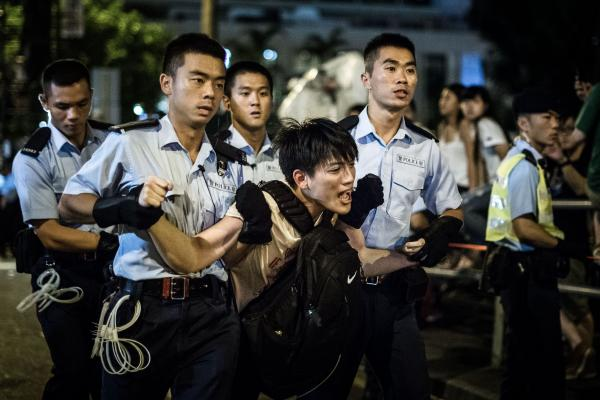 Police remove a protester during a pro-democracy rally early on July 2 in Hong Kong. Frustration is growing over the influence of Beijing on the city and its press.