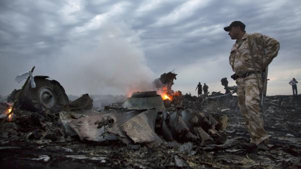 People walk amid debris Thursday at the crash site of Malaysia Airlines Flight MH17 near the village of Grabovo, Ukraine.