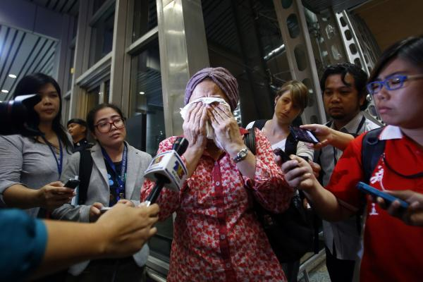 A woman at Kuala Lumpur International Airport reacts to news of the crash.