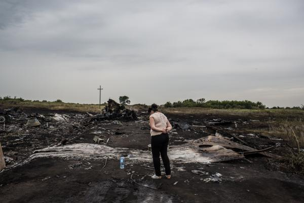 A woman looks at the wreckage in Grabovka. Parts of the crash site were still smoldering Friday. <br /><br />