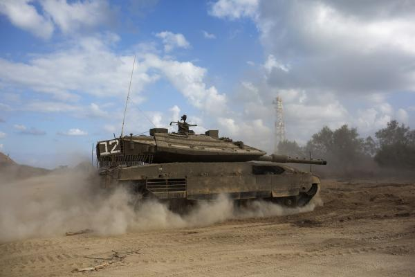 An Israeli tank advances near the Israel-Gaza Strip border on Friday as part of Israel's ground incursion in the territory. Israel launched the ground operation Thursday following more than a week of airstrikes that did not halt Palestinian rocket fire.