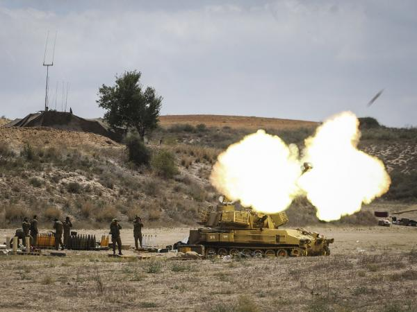 Israeli troops fire a shell Friday into Gaza from their position just outside the territory, near Sderot, Israel.