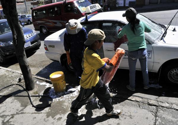 A boy helps his older siblings to wash a car in a street of La Paz, Bolivia, on May 7. Bolivian children work on farms, in mines, and other dangerous jobs for children. Now, child labor is officially legalized in the country. (Aizar Raldes/AFP/Getty Images)