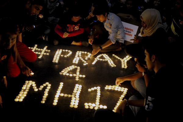 People arrange candles for the victims of Flight MH17 at a shopping mall in Petaling Jaya, Malaysia. The flight was on its way to the Malaysian capital from Amsterdam.