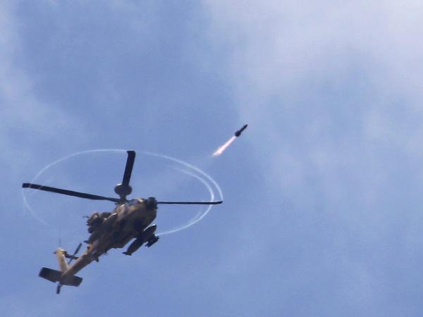An Israeli Apache helicopter fires a missile toward the Gaza Strip on Saturday as Israeli forces pressed ahead with a ground offensive.