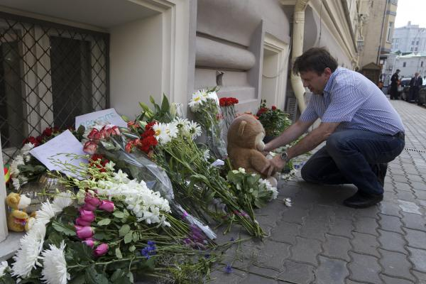 A man lays a stuffed bear among flowers outside the Dutch Embassy in Moscow.