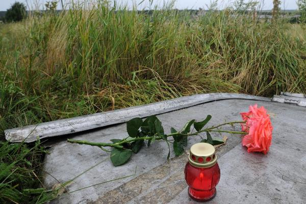 A candle and a rose are placed on a piece of debris at the site of the crash.