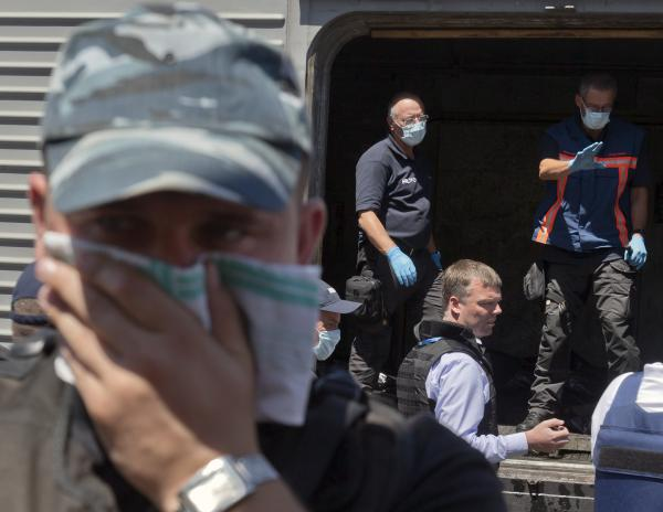 Deputy head of the OSCE mission to Ukraine Alexander Hug (center right) stands outside a refrigerated train as members of the Netherlands' National Forensic Investigations Team inspect bodies.