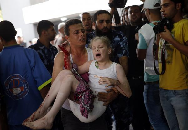 A Palestinian carries a wounded girl in the emergency room of Shifa Hospital in Gaza City. The city's main hospital is filled with the wounded, and many others have taken refuge on the hospital grounds.