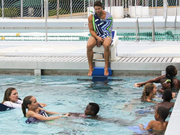 Five kids from South Miami work on their swimming skills before playing a game of sharks and minnows.