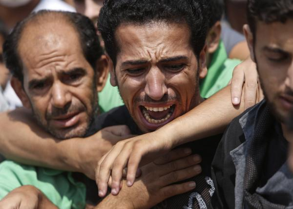 A relative bursts into tears in front of the bodies of seven members of the Kelani family, killed overnight by an Israeli strike in Gaza City.