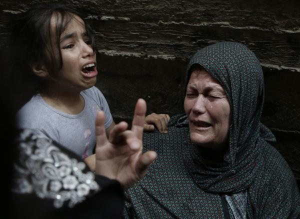Palestinian relatives of Hasan Baker, 60-years-old, grieve during his funeral in Gaza City, on July 22, 2014. A series of Israeli air strikes early killed seven people in Gaza, including five members of the same family, emergency services spokesman Ashraf al-Qudra said. (Mohammed Abed/AFP/Getty Images)