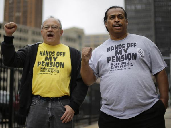 Retirees Mike Shane (left) and William Davis protest near the federal courthouse in Detroit on July 3. Workers and retirees approved pension cuts in Detroit's bankruptcy by a landslide, the city reported Monday.