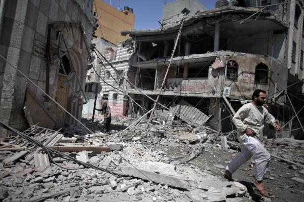 Palestinians walk through the rubble of houses in Gaza City minutes after they were hit in an Israeli strike on Wednesday.