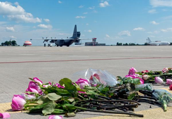 Flowers lay on the tarmac as a ground Hercules transport aircraft of the Royal Netherlands Air Force, carrying bodies from downed Malaysia Airlines Flight MH17, prepared to take off Wednesday in Kharkiv, Ukraine.