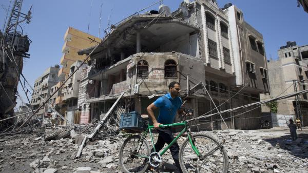 A Palestinian man pushes his bicycle amid debris following an Israeli military strike in Gaza City on Wednesday. While Israel and Hamas have clashed repeatedly in Gaza, the West Bank has been comparatively calm in recent years.