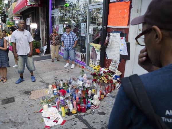 Pedestrians stand beside a memorial for Eric Garner, a Staten Island man who died while being arrested by New York City police.