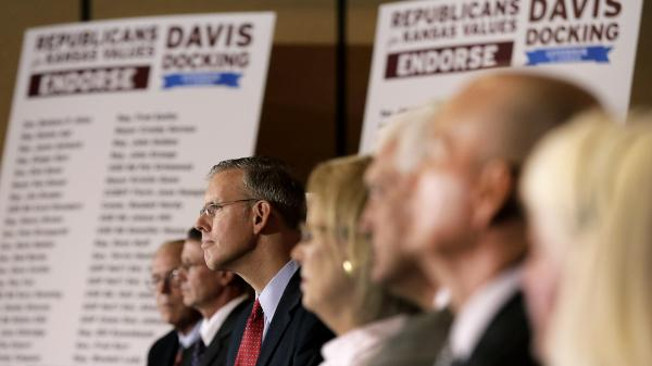 Paul Davis, third from left, the presumed Democratic nominee for Kansas governor, receives the endorsements of more than 100 current and former Republican politicians on July 15, 2014, in Topeka, Kan.