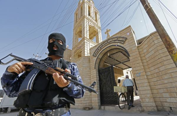 An Iraqi security officer, stands guard outside the Church of the Virgin Mary in the northern town of Bartala, on June 15, 2012, east of the northern city of Mosul. (Karim Sahib/AFP/Getty Images)