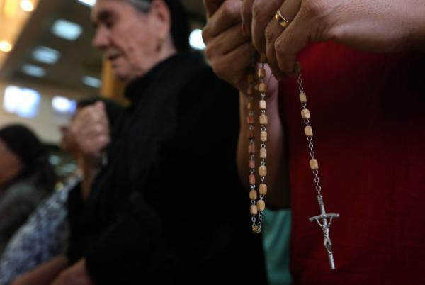An Iraqi Christian holds a rosary during a mass at the Saint-Joseph church in Arbil, the capital of the autonomous Kurdish region of northern Iraq, on July 20, 2014. Hundreds of Christian families fled their homes in Mosul on July 20, 2014 as a jihadist ultimatum threatening their community's centuries-old presence in the northern Iraqi city expired. (Safin Hamed/AFP/Getty Images)