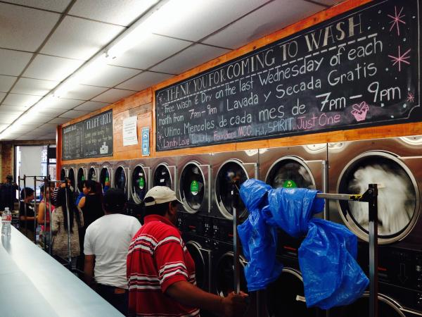 People who have come to do laundry with mingle with volunteers at a laundromat in East Hollywood, Calif. The Laundry Love initiative raises money to help the poor pay for the cost of laundry.