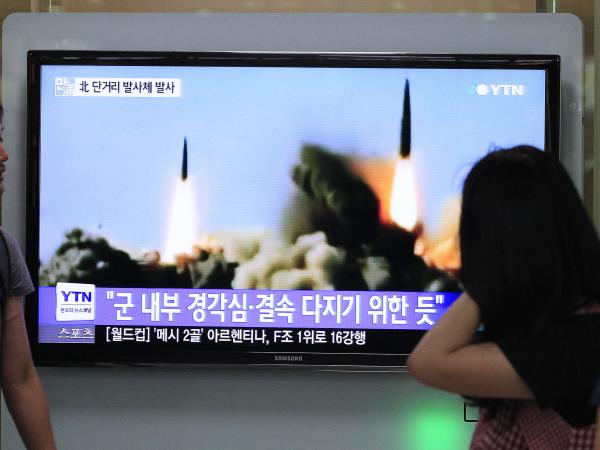 South Koreans at the Seoul train station watch a TV news program showing a June missile launch conducted by the North.