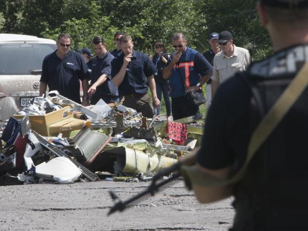 Dutch and Australian investigators along with members of the OSCE mission in Ukraine examine pieces of the crashed Malaysia Airlines Flight 17 in the village of Petropavlivka, Donetsk region, in eastern Ukraine on Friday.