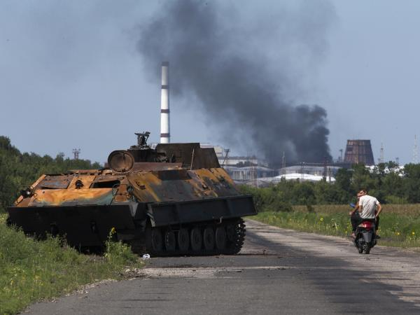 A smoldering rebel APC near the city of Lisichansk, Luhansk region, eastern Ukraine, on  Saturday. Fighting farther south, near the city of Donetsk, has prevented investigators from reaching the wreckage of MH17.