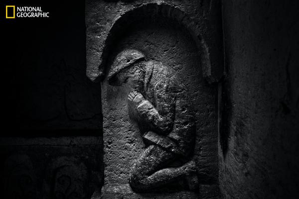 A hundred years ago in a subterranean chapel, an unknown artist carved this image of a French soldier praying. (From the August issue of National Geographic magazine, © Jeffrey Gusky/National Geographic)