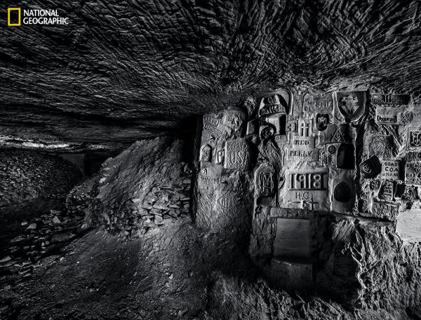 "U.S. troops of the 26th ""Yankee"" Division, billeted in an underground quarry at Chemin des Dames, carved some 500 engravings during six weeks in 1918. These include names, addresses, religious and patriotic symbols, and other images. (From the August issue of National Geographic magazine, © Jeffrey Gusky/National Geographic)"