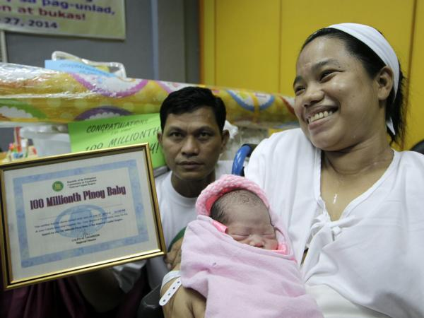 "Filipino Clemente Sentino Jr (L), 45 and Dailin Cabigayan (R), 27 holds their 6 lbs newborn baby girl marking the ""100 million population of the Philippines."""