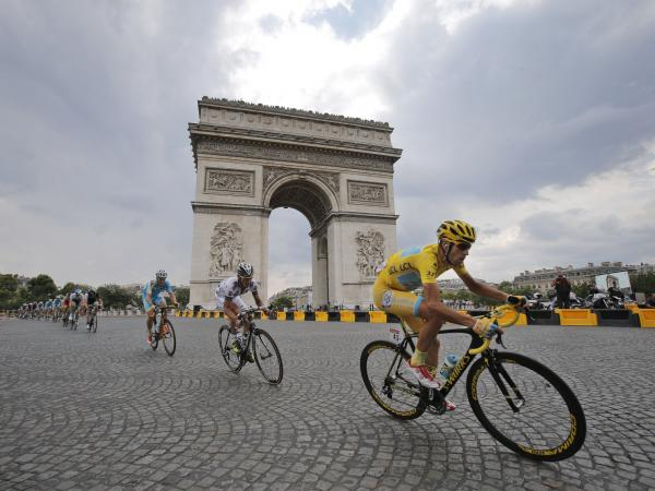 Italy's Vincenzo Nibali, wearing the overall leader's yellow jersey, passes the Arc de Triomphe during the twenty-first and last stage of the Tour de France cycling race over 85.4 miles with start in Evry and finish in Paris, France.