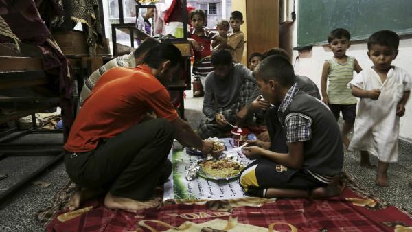 Members of a Palestinian family break their fast with the iftar meal during the holy month of Ramadan at a United Nations school, where hundreds of families have sought refuge after fleeing their homes following fighting between Israeli forces and Hamas.