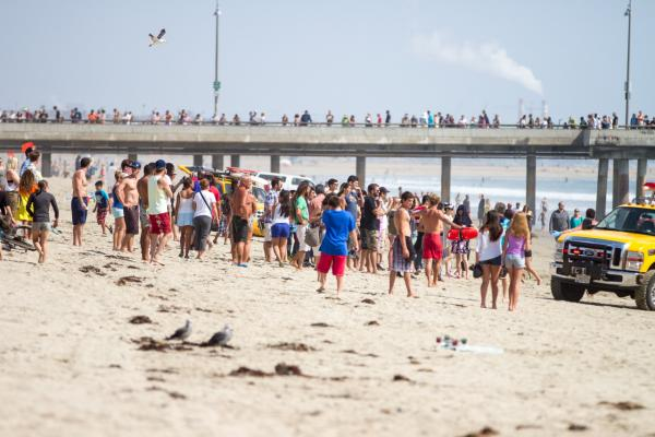 Pedestrians and beachgoers stand on the shore near Venice Beach as lifeguards, right, bring in a swimmer rescued from the water after a lightening strike Sunday July 27, 2014 in Los Angeles. (Steve Christensen/AP)
