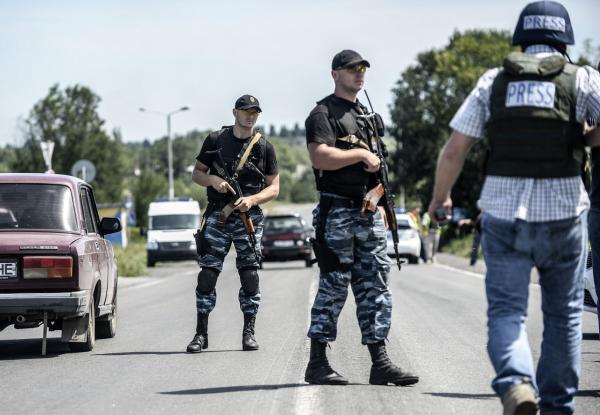 Pro-Russian militants block the road behind Dutch and Australian forensic teams on their way to the crash site of the Malaysia Airlines flight MH17 on July 28, 2014 in Donetsk. Dutch and Australian forensic investigators turned back on their way to the MH17 crash site on July 28, after 'explosions' in the area, a government spokeswoman in The Hague said. (Bulent Kilic/AFP/Getty Images)