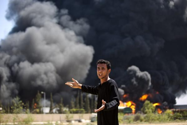A Palestinian man reacts as flames engulf the fuel tanks of the only power plant supplying electricity to the Gaza Strip after it was hit by overnight Israeli shelling, on July 29, 2014, in the south of Gaza City. The damage of the power plant exacerbated the heavy damage to civilian infrastructure in Gaza already inflicted during the 22 days of the Israeli offensive. (Mahmud Hams/AFP/Getty Images)
