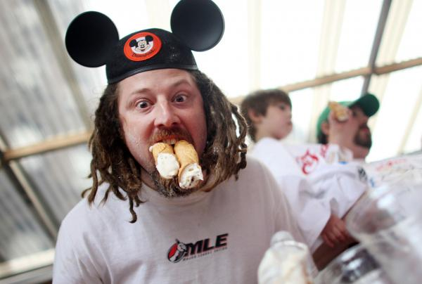 """Crazy Legs"" Conti poses with cannolis after winning the eighth annual Little Italy Cannoli Eating Competition on September 10, 2009 in New York City. He devoured 20.5 cannolis in six minutes. (Mario Tama/Getty Images)"