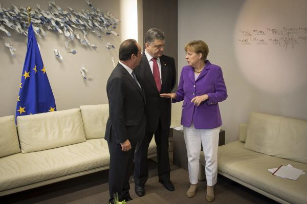 In this handout photo provided by the German Government Press Office (BPA), French President Francois Hollande, Ukrainian President Petro Poroshenko, and German Chancellor Angela Merkel chat at the EU summit after the signing of the EU's Association Agreement with Ukraine on June 27 in Brussels, Belgium. The landmark agreement will mean that the Ukraine will need to adhere to European values such as democracy and human rights. (Guido Bergmann/Bundesregierung via Getty Images)