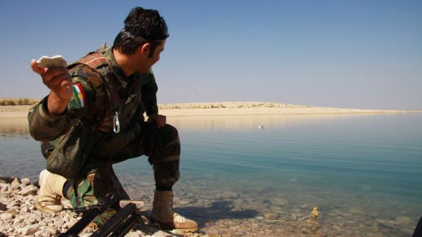 A Kurdish peshmerga soldier skims a stone across the Mosul dam lake on the Tigris river in northern Iraq. The rivers there — the Tigris and the Euphrates — are a source of pride for Iraqis, who in Arabic refer to their country as the land of two rivers.